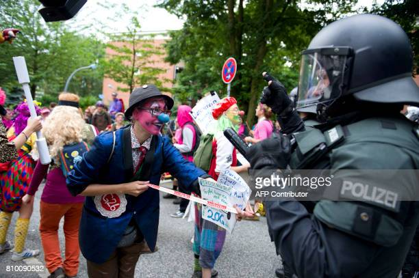TOPSHOT Demonstrators dressed as clowns face policemen as they take part in a protest titled '#BlockG20 Color the Red Zone' on July 7 2017 in Hamburg...