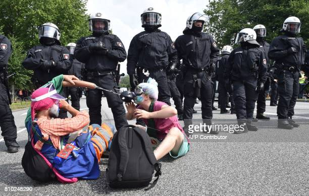 Demonstrators dressed as clowns perform next to policemen during a protest on July 7 2017 in Hamburg northern Germany where leaders of the world's...