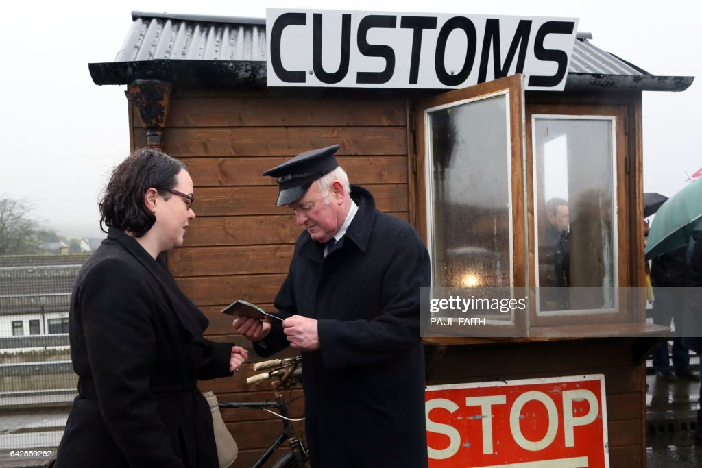 Demonstrators dressed as custom officials set up a mock customs checkpoint at the border crossing in Killeen, near Dundalk to protest against the potential introduction of border checks following the decision by the UK to leave the EU on February 18, 2017. / AFP / Paul FAITH