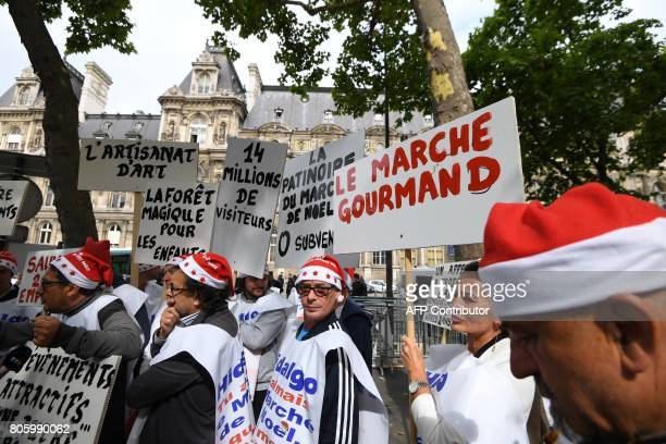 Demonstrators dressed as Santa Claus carry signs and chant slogans during a protest against the planned closure of the Champs Elysee Christmas...
