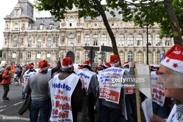 Demonstrators dressed as Santa Claus wear placards reading 'Hidalgo do not kill the Christmas market' during a protest against the planned closure of...