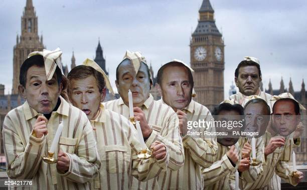 Demonstrators dressed as Scrooge and wearing masks depicting the leaders of the G8 countries protest outside Parliament in London The Government was...