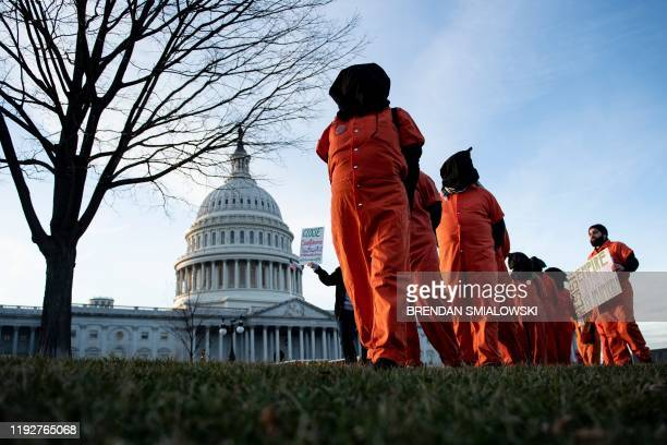 "Demonstrators dressed in Guantanamo Bay prisoner uniforms march past Capitol Hill in Washington, DC, on January 9 during a rally on ""No War with..."