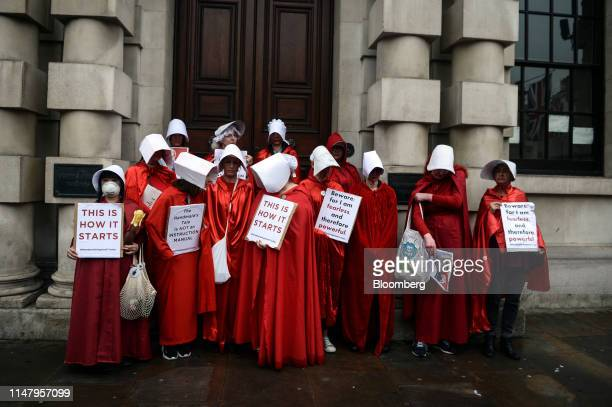 Demonstrators dressed in Handmaid's Tale costumes hold antiTrump placards during a demonstration in London UK on Tuesday June 4 2019 With the country...