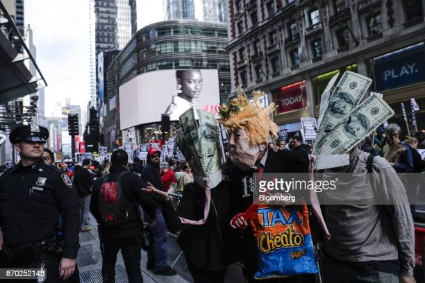 Demonstrators dressed in the likeness of US President Donald Trump and 100 dollar banknotes participate in 'The Trump/Pence Regime Must Go' rally in...