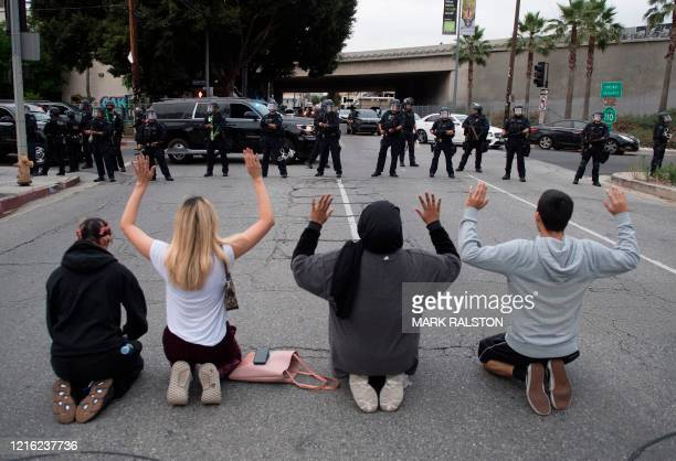 Demonstrators face a row of police as they block a road leading to the 110 freeway to protest the death of George Floyd in downtown Los Angeles...