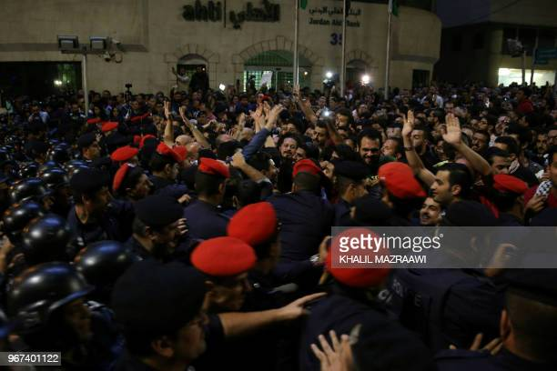 TOPSHOT Demonstrators face Jordanian antiriot police and security forces during a protest in Amman Jordan near the prime minister's office on June 4...