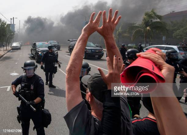 Demonstrators face off with police while a car burns in the Fairfax District as they protest the death of George Floyd, an unarmed black man who died...