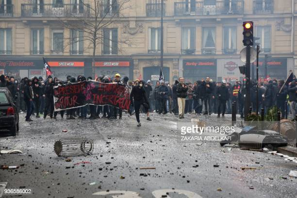 Demonstrators face policemen during clashes as part of a protest against French government's string of reforms on March 22 2018 in Paris Seven trade...
