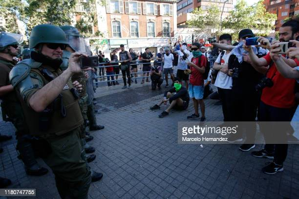 Demonstrators film with their phones the riot police officers during a protest against the government of president Sebastian Piñera on November 7...