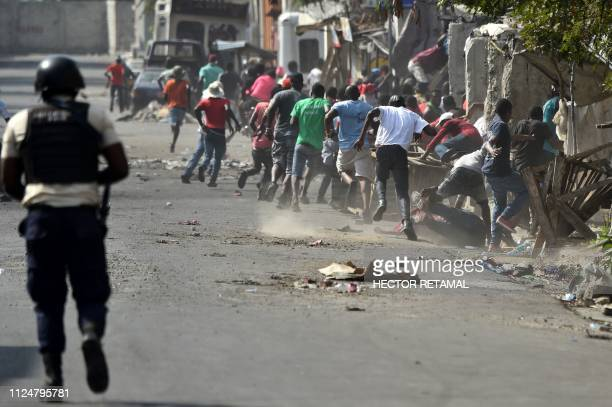 Demonstrators flee as Haitian Police open fire during the clashes in the centre of Haitian Capital PortauPrince February 13 2019 This is the seventh...