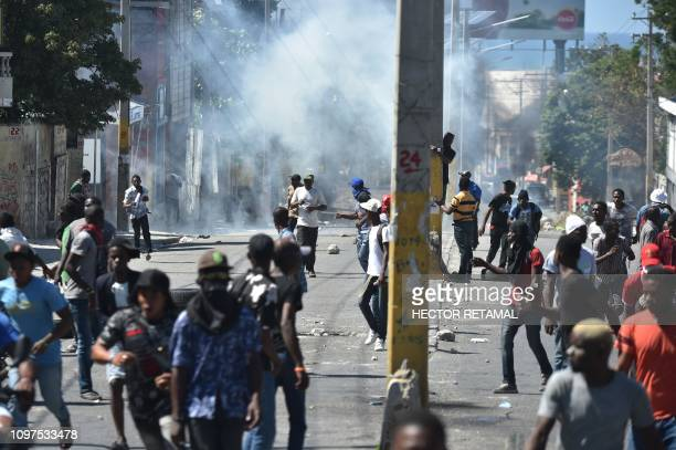Demonstrators flee from teargas fired by Haitian Police during the fourth day of protests in PortauPrince on February 10 2019