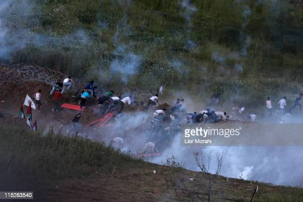 Demonstrators flee Israeli fired tear gas as they gather along Syria's border with Israel while trying to cut through a line of barbed wire and head...