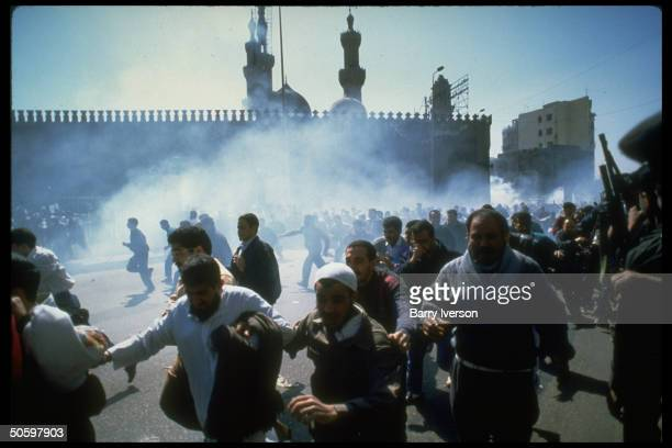 Demonstrators fleeing tear gas fired into crowd by riot police after prayers protest against massacre of Muslims by Jewish settler in Hebron nr Al...