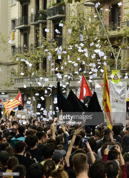 Demonstrators flip ballots as they protest called by CNT union in front of the Catalan Popular Party headquarters during a general strike in...