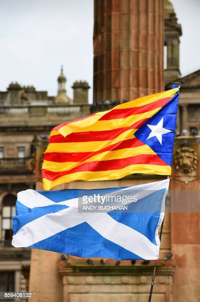 Demonstrators fly the Catalan proindependence 'Estelada' flag and the Flag of Scotland the Saltire during a protest to show solidarity with Catalonia...