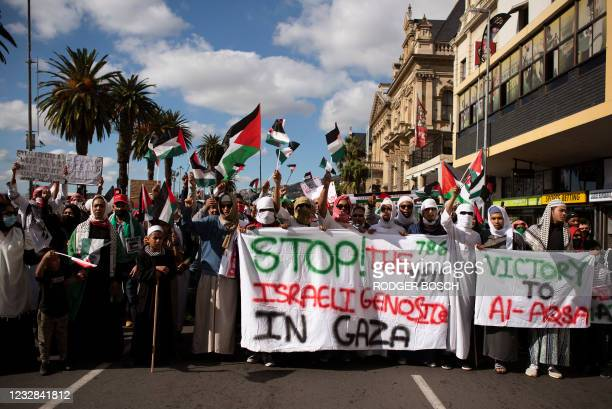 Demonstrators from a variety of political parties and social movements hold banners and Palestinian flags as they march through the city centre in...