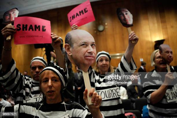 Demonstrators from Code Pink for Peace hold photographs of Lloyd Blankfein chairman and CEO of The Goldman Sachs Group and demand he be jailed with...