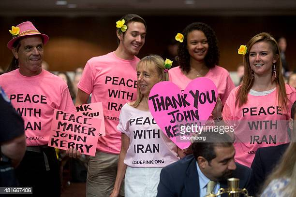 Demonstrators from Code pink hold signs in support of John Kerry US secretary of state not pictured before the start of a Senate Foreign Relations...
