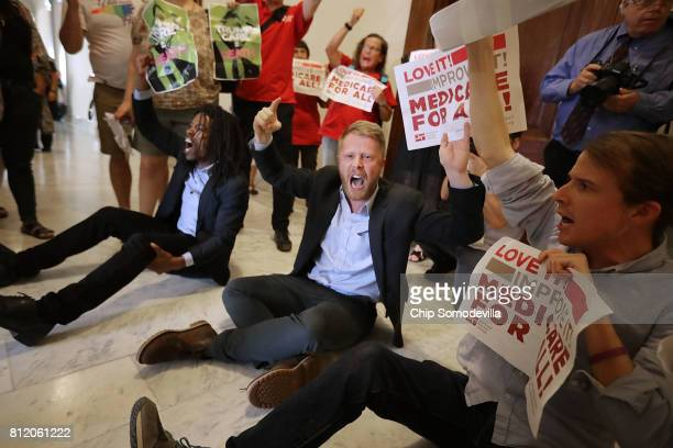 """Demonstrators from Texas sit on the ground and chant, """"Kill the bill, kill the bill,"""" outside the offices of Sen. Ted Cruz while protesting against..."""