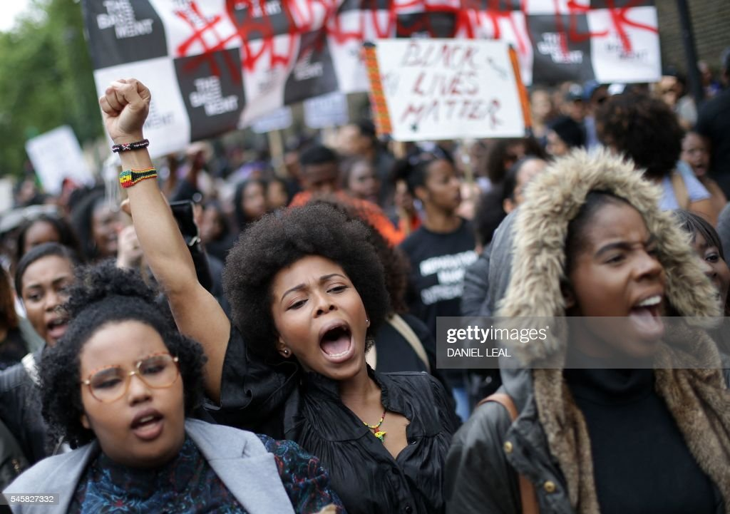 Demonstrators from the Black Lives Matter movement march through central London on July 10, 2016, during a demonstration against the killing of black men by police in the US. Police arrested scores of people in demonstrations overnight Saturday to Sunday in several US cities, as racial tensions simmer over the killing of black men by police. / AFP / DANIEL