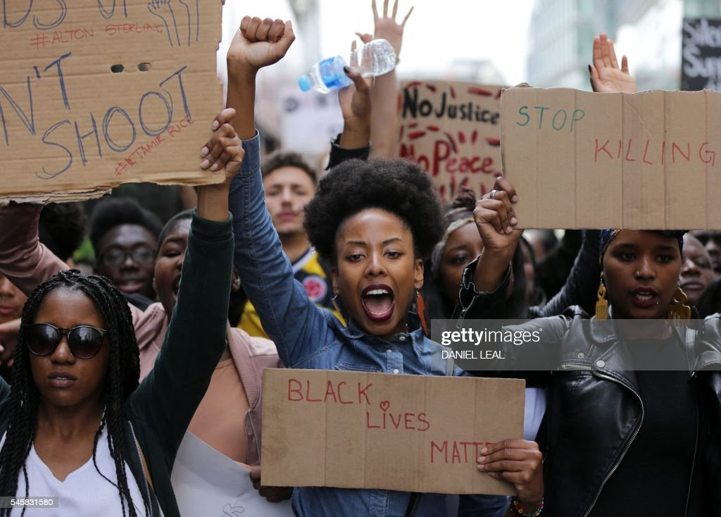 TOPSHOT - Demonstrators from the Black Lives Matter movement march through central London on July 10, 2016, during a demonstration against the killing of black men by police in the US. Police arrested scores of people in demonstrations overnight Saturday to Sunday in several US cities, as racial tensions simmer over the killing of black men by police. / AFP / DANIEL