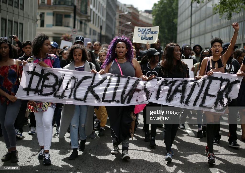 Demonstrators from the Black Lives Matter movement march through the streets of central London on July 10, 2016, during a demonstration against the killing of black men by police in the US. Police arrested scores of people in demonstrations overnight Saturday to Sunday in several US cities, as racial tensions simmer over the killing of black men by police. / AFP / DANIEL
