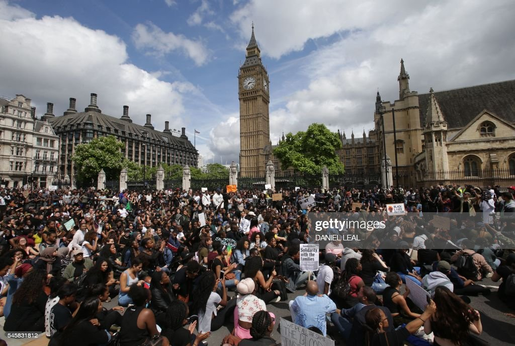 Demonstrators from the Black Lives Matter movement sit in the road on Parliament Square in central London on July 10, 2016, during a demonstration against the killing of black men by police in the US. Police arrested scores of people in demonstrations overnight Saturday to Sunday in several US cities, as racial tensions simmer over the killing of black men by police. / AFP / DANIEL