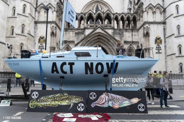 TOPSHOT Demonstrators from the Extinction Rebellion climate environmental activist group protest outside of The Royal Courts of Justice on The Strand...
