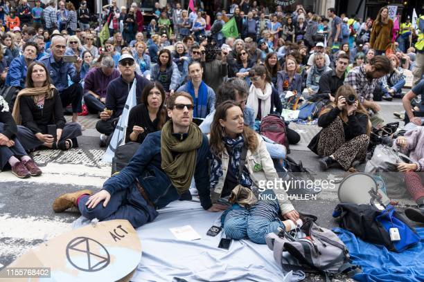Demonstrators from the Extinction Rebellion climate environmental activist group listen to speakers as they protest outside of The Royal Courts of...