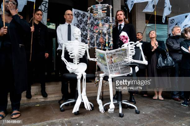 TOPSHOT Demonstrators from the Extinction Rebellion climate environmental activist group take part in a protest outside the offices of UK newspapers...