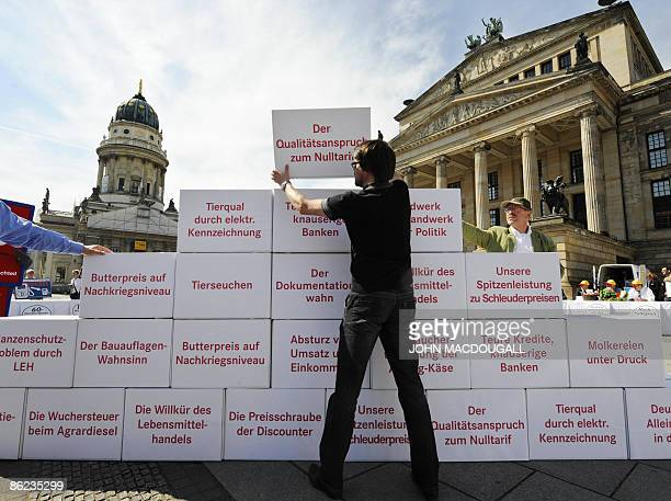 Demonstrators from the German Farmers' Association build a pyramid of grievances during a protest at Berlin's Gendarmenmarkt square April 27 on the...