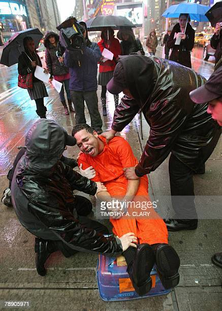 Demonstrators from the group 'World Can't Wait' hold a mock waterboarding torture of a prisioner in Times Square 11 January 2008 to mark the sixth...