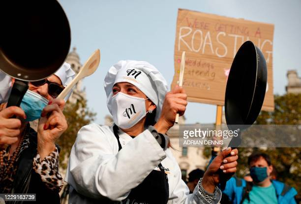 Demonstrators from the hospitality industry some wearing a face mask or covering due to the COVID19 pandemic gather to protest against the...