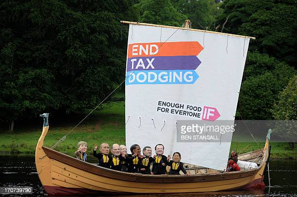 Demonstrators from the 'IF campaign' wearing masks depicting G8 leaders protest against tax avoidance during the G8 Summit in Enniskillen in Northern...