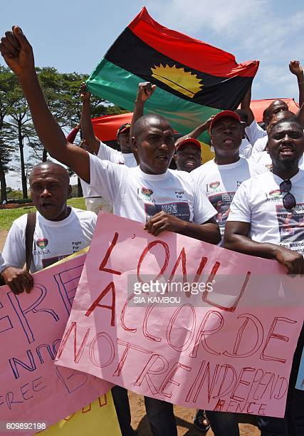 Demonstrators from the Indigenous People of Biafra group wave flags and hold a sign reading 'The United Nations grants us independence' during a...