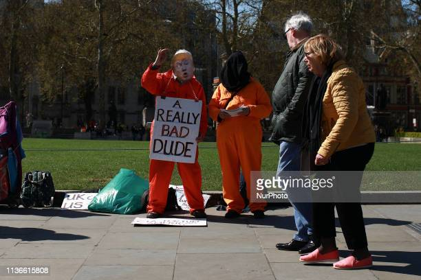 Demonstrators from the London Guantanamo Campaign wearing a Donald Trump mask a black hood and orange prison jumpsuits protest outside the Houses of...