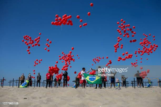 Demonstrators from the NGO 'Rio De Paz' hold release red balloons in Copacabana beach on August 8, 2020 in Rio de Janeiro, Brazil. The demonstration...