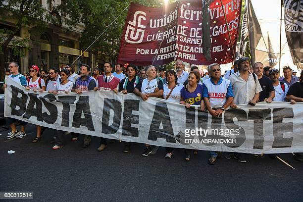 Demonstrators from the railway union hold a placcard as they march for the 15th anniversary of ousting of former President Fernando de la Rua in...