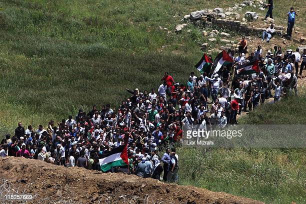 Demonstrators gather along Syria's border with Israel before trying to cut through a line of barbed wire and head into the Israeli-annexed Golan...