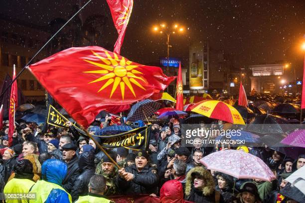 Demonstrators gather and hold Macedonian flags during a protest against a process of renaming the country North Macedonia, in front of the Parliament...