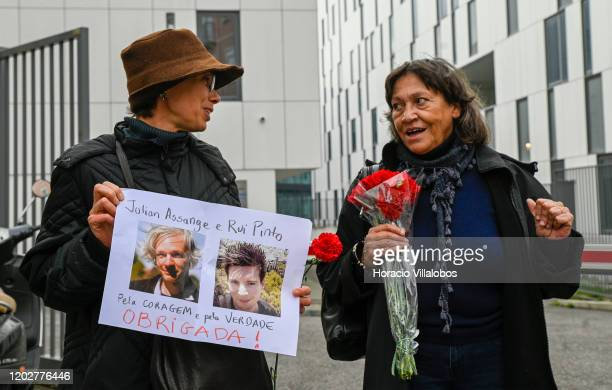Demonstrators gather holding red carnations and a sign supporting Rui Pinto and Julian Assange outside the Lisbon Judicial Police Prison to demand...