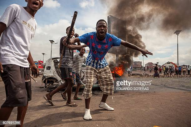 TOPSHOT Demonstrators gather in front of a burning car during an opposition rally in Kinshasa on September 19 2016 Police fired tear gas at scores of...