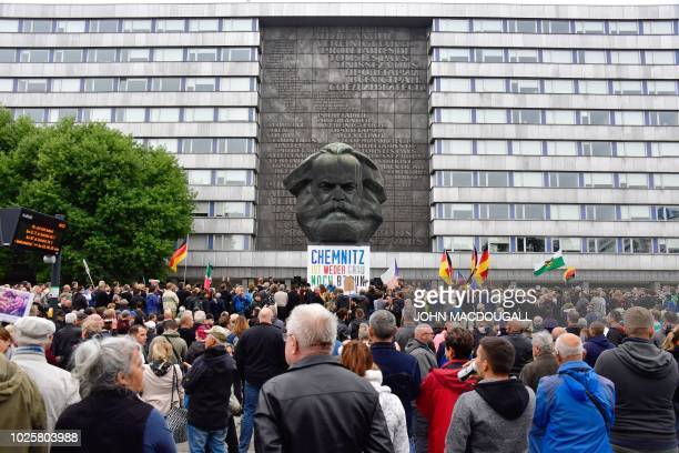 Demonstrators gather in front of the Karl Marx monument where a poster is fixed reading Chemnitz is neither grey nor brown during a protest organised...