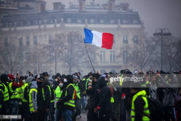 Demonstrators gather near the Arc de Triomphe as a French flag floats during a protest of Yellow vests against rising oil prices and living costs, on...