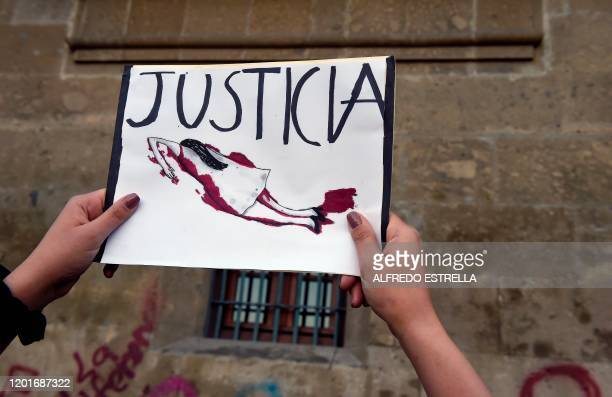 Demonstrators gather outside the National Palace, in Mexico City, on February 18 to protest gender violence. - Dozens of women protested Tuesday over...