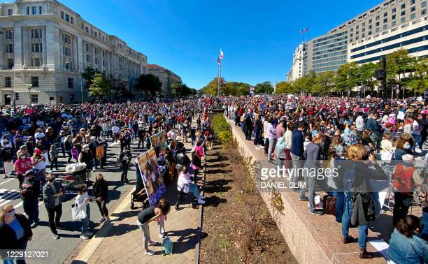 Demonstrators gather to take part in the nationwide Women's March on October 17 at Freedom Plaza in Washington, DC.