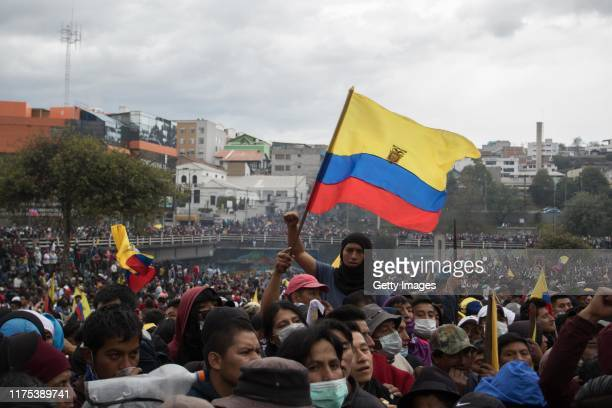 Demonstrators gather waving Ecuadorian flags near the National Assembly in an attempt to dialogue with the police during the protests against the...