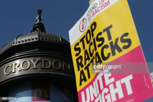 Demonstrators gather with placards during a protest called by the 'Stand Up To Racism' group in Croydon south London on April 8 2017 following the...