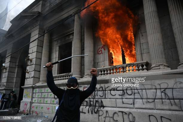 Demonstrators gesture after setting on fire an office of the Congress building during a protest demanding the resignation of President Alejandro...